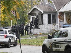 Toledo police rush a Montrose Avenue home where they were alerted by K-9 unit to the presence of a suspect in an armed robbery. Police released a stun grenade prior to entering on Friday.