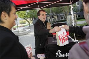 Liz Simon, left, jokes with Brandon Hirn, an assistant manager at Chick-fil-A, center, while he serves another customer during lunchtime. Several food trucks have set up near the corner of Madison and St. Clair streets on Tuesdays and Thursdays from 11 a.m. to 1:30 p.m.
