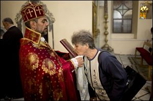 In this photograph made on Sunday, Oct. 27, 2013, a woman kisses the Bible during a service in an Armenian Orthodox church in Damascus, Syria.