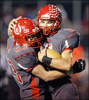 Bedford High School players Dillon Folk (53) and Alec Hullibarger (11) celebrate Hullibarger's  touchdown.