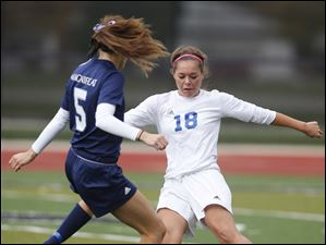 Anthony Wayne's Baily Hertzfeld (18) moves the ball against  Rocky River Magnificat's Anne Ubbing (5).