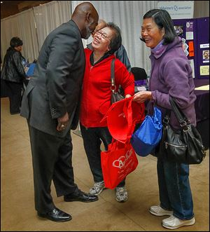 Toledo Mayor Mike Bell is greeted by Wan Sung Leung during the annual Caregiver Expo at Parkway Plaza in Maumee, one of several events on his calendar Saturday.