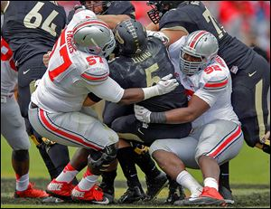 Purdue quarterback Danny Etling is sacked by Ohio State's Chase Farris, left, and Adolphus Washington. The Buckeyes had six sacks.
