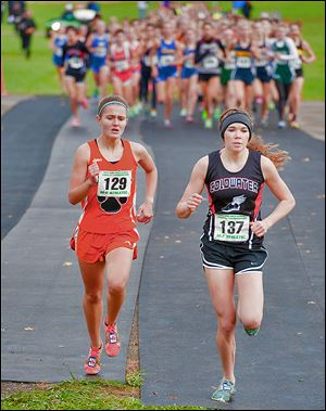 Brittany Atkinson, left, of Liberty Center looks to pass Sarah Kanney of Coldwater at the Division III state meet. Atkinson won in 18 minutes, 31.45 seconds.