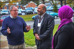 D. Michael Collins, left, talks with Ziad Hummos, center, board member of the Al-Madinah Community Center, and Maria Azzouni, the center's vice president. Mr. Collins spent much of the final Saturday before the election making campaign stops, but his door-to-door efforts were curtailed by the weather.