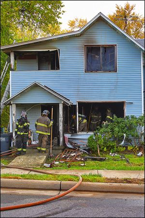Firefighters knock down areas of a smoldering wall at 458 Fassett St. in East Toledo. The fire broke out Saturday and crews were called about 1:17 p.m., officials reported.