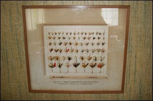 A framed display of some of the more popular fly patterns used to catch trout from Cold Creek hangs in the formal dining room of the farmhouse.
