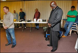 Mayor Mike Bell prays with church members at a men's prayer breakfast at Westside Church in Toledo.