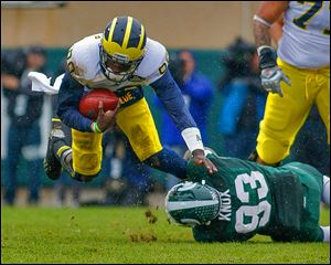 Michigan quarterback Devin Gardner is tripped up by Michigan State's Damon Knox on Saturday at Spartan Stadium.