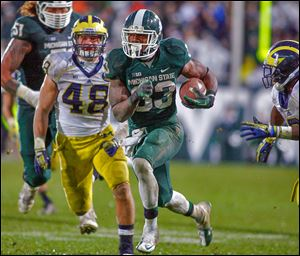 Michigan State's Jeremy Langford runs between Michigan's Desmond Morgan, left, and Raymon Taylor for a 40-yard fourth-quarter touchdown.