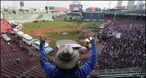Carlos Arredondo raises his arms as he waves to fans at Fenway Park in advance of the Boston Red Sox's championship parade today in celebration of the baseball team's World Series win.