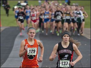 Brittany Atkinson (129) of Liberty Center runs with Sarah Kanney (137)  of Coldwater near the start of the race.