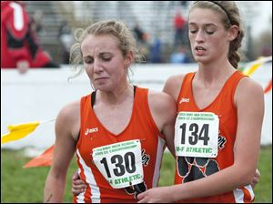 Liberty Center runners Emma Babcock, (130) and Rachael Pinson (134) leave the track after finishing.