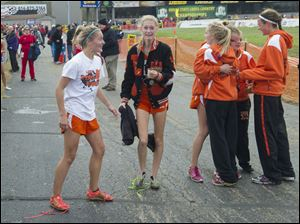 Liberty Center runners Brittany Atkinson, left, Paige Chamberlain, Sarah Knapp, back to camera, Rachael Pinson Emma Babcock and Olivia Kundo celebrate after hearing the announcement that they won  the Ohio High School Girls Div. III cross country championships.
