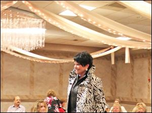 Bonnie Wrobel on the runway wearing a signature animal print coat with stand up ruffled collar from Ragazza.