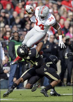 Ohio State running back Carlos Hyde leaps over Purdue defensive back Frankie Williams, left, and safety Taylor Richards during the first half Saturday in West Lafayette, Ind.