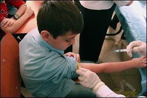 A Syrian student receives a vaccination as part of a UNICEF-supported vaccination campaign at a school in Damascus.