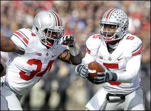 Ohio State quarterback Braxton Miller, right, fakes a handoff to running back Carlos Hyde during the first half Saturday at Purdue in West Lafayette, Ind. The Buckeyes are one of five unbeaten teams from power conferences.