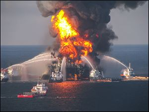 U.S. Coast Guard crews spray water on BP's Deepwater Horizon offshore oil rig in 2010. The blast killed 11 people and spurred a massive oil spill in the Gulf.