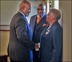 Mayor Mike Bell, left, and Calvin Lawshe, city economic development commissioner, say good-bye to Lillie Winston, chief usher, after services at Jerusalem Missionary Baptist Church.