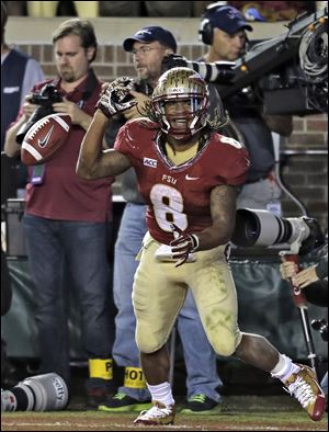 Florida State running back James Wilder, Jr., celebrates after scoring a touchdown against Miami on Saturday night in Tallahassee. Florida State is back in second place in the BCS standings, edging past Oregon behind first-place Alabama.