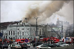 Fire fighters work at the site of a fire today at the building of the School of Modern Drama theater in Moscow.
