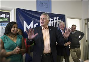 Virginia gubernatorial candidate Terry McAuliffe, center, speaks to his supporters and encourages them to make the final push by knocking on door-to-door to get more votes on Saturday in Norfolk, Va.