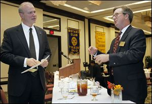Roger Wood, president and CEO of Dana Holding Corp., left, speaks with Keith Burwell of the Rotary Community Foundation, after the Toledo Rotary Club  meeting at the Park Inn hotel downtown.