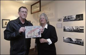 John Huss and Lisa Swickard, at a coffee house in Tiffin, hold a rendition of the cover of their book on the razing of the Seneca County Courthouse.