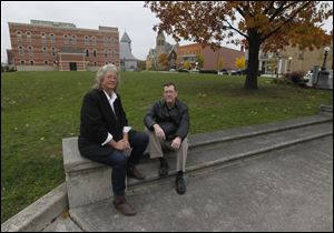 Lisa Swickard and John Huss sit on the steps of what used to be the Seneca County Courthouse in Tiffin. The amateur photographers are raising funds to pay for the publication of their book about the destruction of the courthouse.