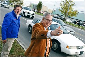 D. Michael Collins greets motorists in front of General Motors Co.'s Toledo Transmission  plant on West Alexis Road during final voter outreach Monday.