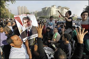 Supporters of Egypt's ousted President Mohammed Morsi raise their hands with four raised fingers, which has become a symbol of the Rabaah al-Adawiya mosque, where Morsi supporters had held a sit-in for weeks that was violently dispersed in August, as one holds his poster during a protest against Morsi's trial in front of the supreme constitutional court in Cairo, Egypt, Monday, Nov. 4, 2013. Egypt's deposed Islamist president was brought from the secret location of his four-month detention to face trial today.