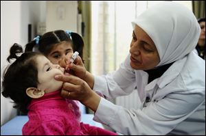 A health worker administers polio vaccine to a child as part of a UNICEF-supported vaccination campaign at the Abou Dhar Al Ghifari Primary Health Care Center in Damascus, Syria, in October.