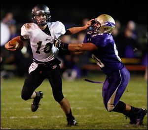 Perrysburg QB Gus Dimmerling (10) runs the ball against  Maumee's Dakota Yeary (60) during a football game last Friday.