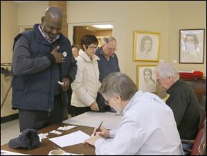 Toledo mayor Mike Bell applies a voting sticker after signing in to vote. Behind him are Tess, center, and Chris McDonnell, all of Toledo.