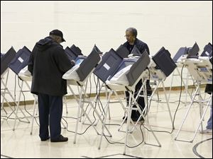 Voters cast their ballots at the polling place at Church of the Cross on Cass Road.
