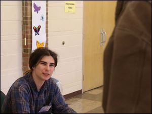 Henry Gray, 17, talks with Greg Haupricht, of Sylvania, as Gray helps check Haupricht in to vote.