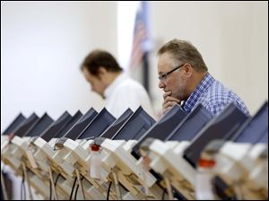 Dave Fitzpatrick looks over his choices as he casts his vote at Garfield Elementary in East Toledo.