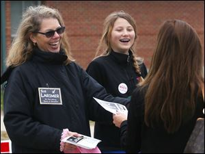 Sue Larimer, a board of education candidate, left, and Shannon Mack, 13, center, hand out literature about Larimer and Shannon's mother Molly Mack, who is running for municipal court judge, outside the Ft. Meigs Elementary polling location in Perrysburg. Both Larimer and Mack said they had hit the polling location at 6:30 a.m. Tuesday in hopes of swaying a few voters last minute.