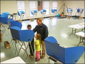 Dan Walendzak, center, votes as his son Connor, 9, left, and daughter Kate, 6, right, watch.