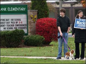 Nathan Rowland Miller, 14, left, held the lead of his six-month-old King Charles Spaniel Rory as the pair joined Nathan's mother Susan Rowland Miller, right, in waving at passing cars outside the Frank Elementary polling location in Perrysburg. The Rowland Millers said they had come out to support their friend Thomas Mackin in his bid for municipal court judge.