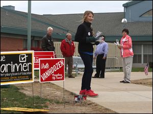 Shannon Mack, 13, center, hands out literature about her mother Molly Mack, who is running for municipal court judge, outside the Ft. Meigs Elementary polling location in Perrysburg.