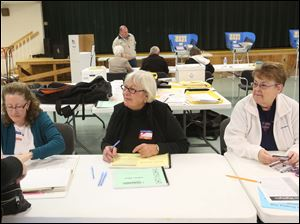 Elizabeth Emmert, left, Kristine Miller, center, and Marsha Meredith, right, help check in voters at the Ft. Meigs Elementary polling location in Perrysburg.
