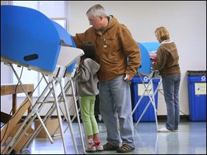 Lily, 7, stands on tip toe to watch her father, Patrick Forrester, center, vote.