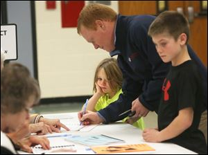 Kate Walendzak, 6, center, waits with her brother Connor, 9, right, as their father Dan, of Perrysburg, center, signs in before voting at the Ft. Meigs Elementary polling location in Perrysburg.