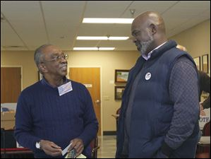 Poll worker Eddie Squaires, J.D., left, talking with Mayor Mike Bell while he waits to vote. Problems with some of the machines meant voters had to wait.