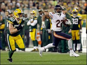 Chicago Bears' Matt Forte runs past Green Bay Packers' A.J. Hawk (50) during the second half.
