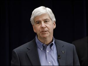 Michigan Gov. Rick Snyder signs into law a measure to charge sex offenders a $50 annual registration fee.