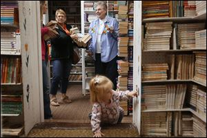 Brooklyn, 1, explores Munchkin Book Store as her mother Jacki Moyer, left, and grandmother, Marlene Baer, both of Archbold, Ohio, center, talk with Barbara Kerschner, right.