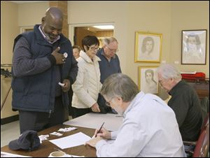 Toledo mayor Mike Bell applies a voting sticker after signing in to vote. Behind him are Tess, center, and Chris McDonnell, both of Toledo.
